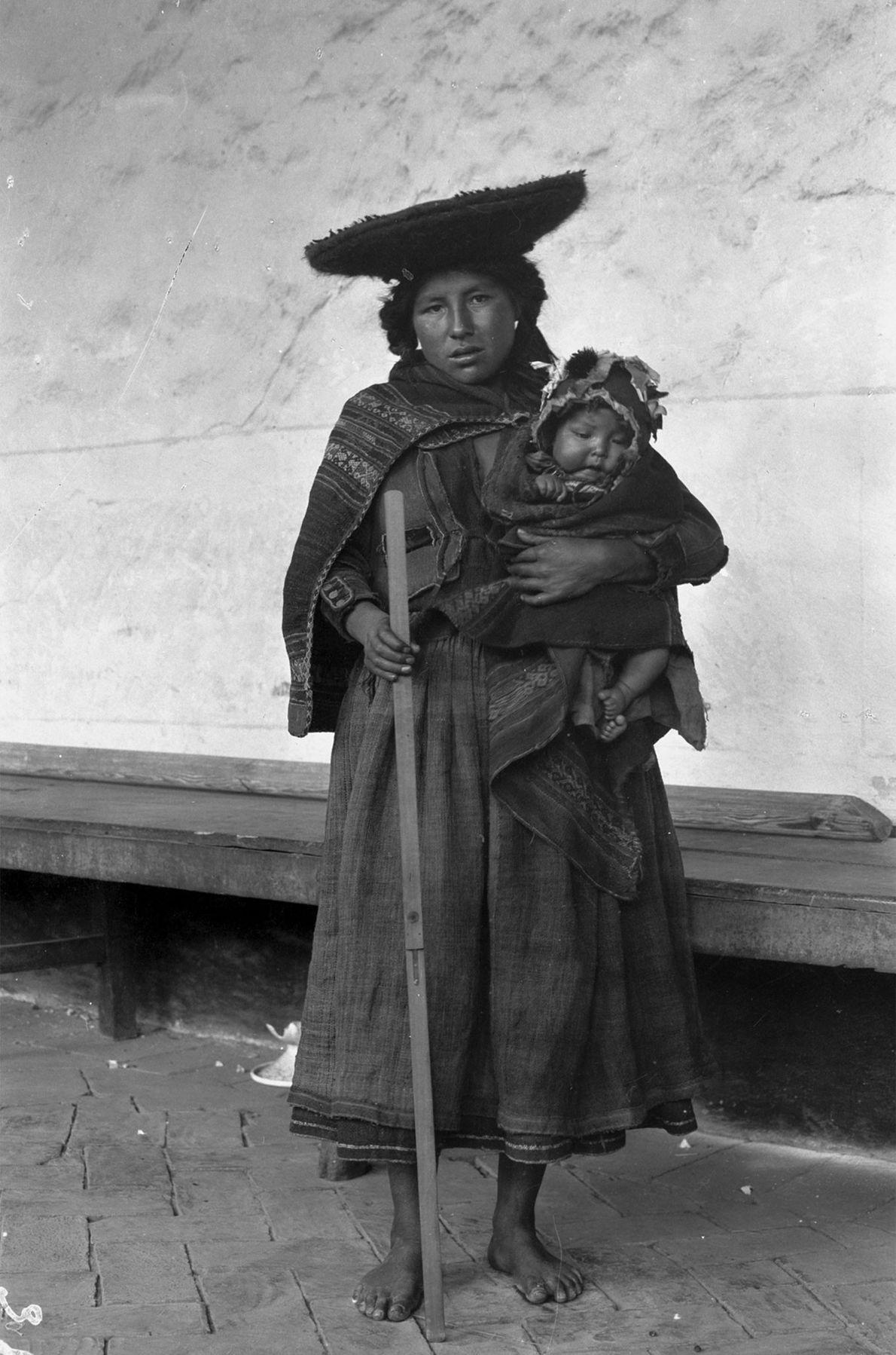 Uma mãe segura seu bebê e uma bitola enquanto posa para uma foto do Vale Cuzco, ...