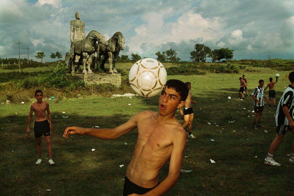 Um menino rebate uma bola de cabeça enquanto joga em um campo.