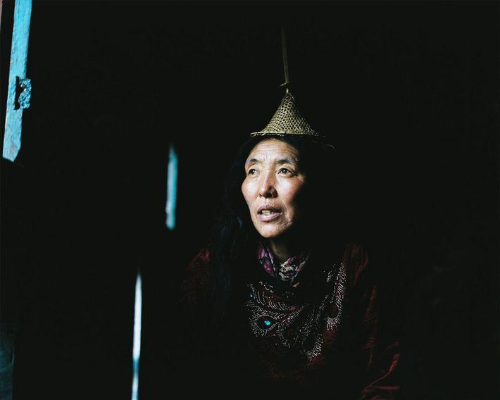 Lham, de 53 anos, olha pela janela de sua casa em Laya.