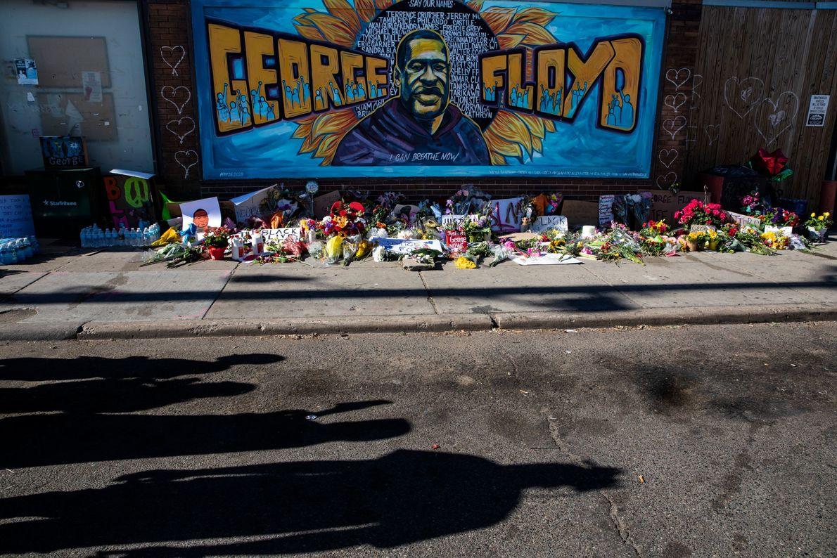 Um mural retratando Floyd voltado para as flores e velas deixadas pelos moradores de Minnesota que ...
