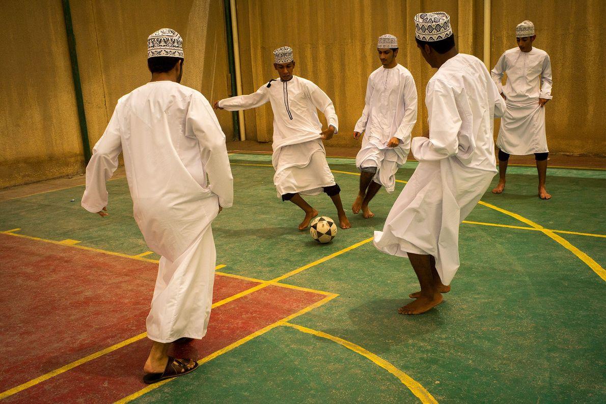 Meninos praticam futebol indoor usando um dishdasha tradicional em Al-Seeb, Omã. Alguns jogadores de futebol indoor ...