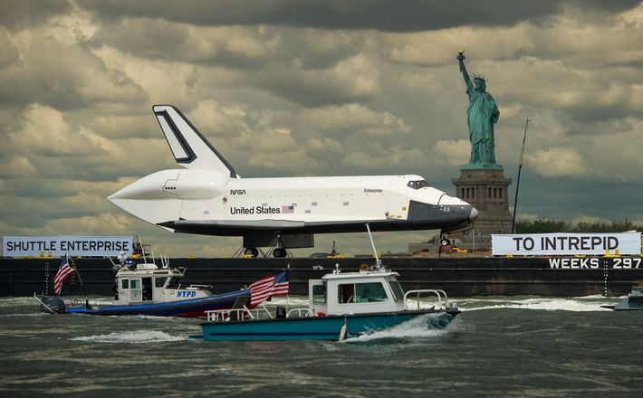 Preso a uma barcaça, o ônibus espacial Enterprise passa pela Estátua da Liberdade aos 6 de ...