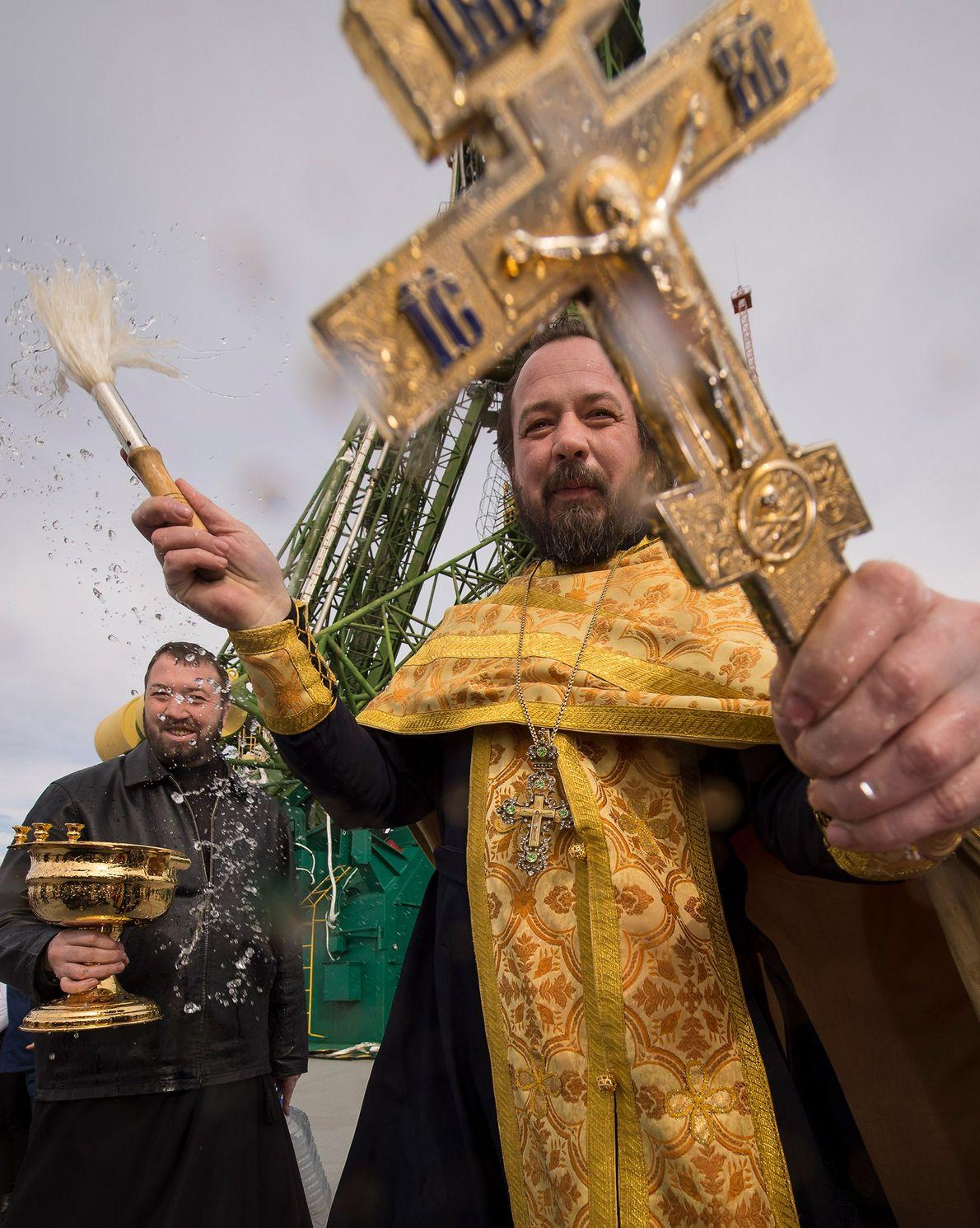 Padre ortodoxo abençoa o pessoal da mídia nas proximidades do foguete Soyuz na plataforma de lançamento ...
