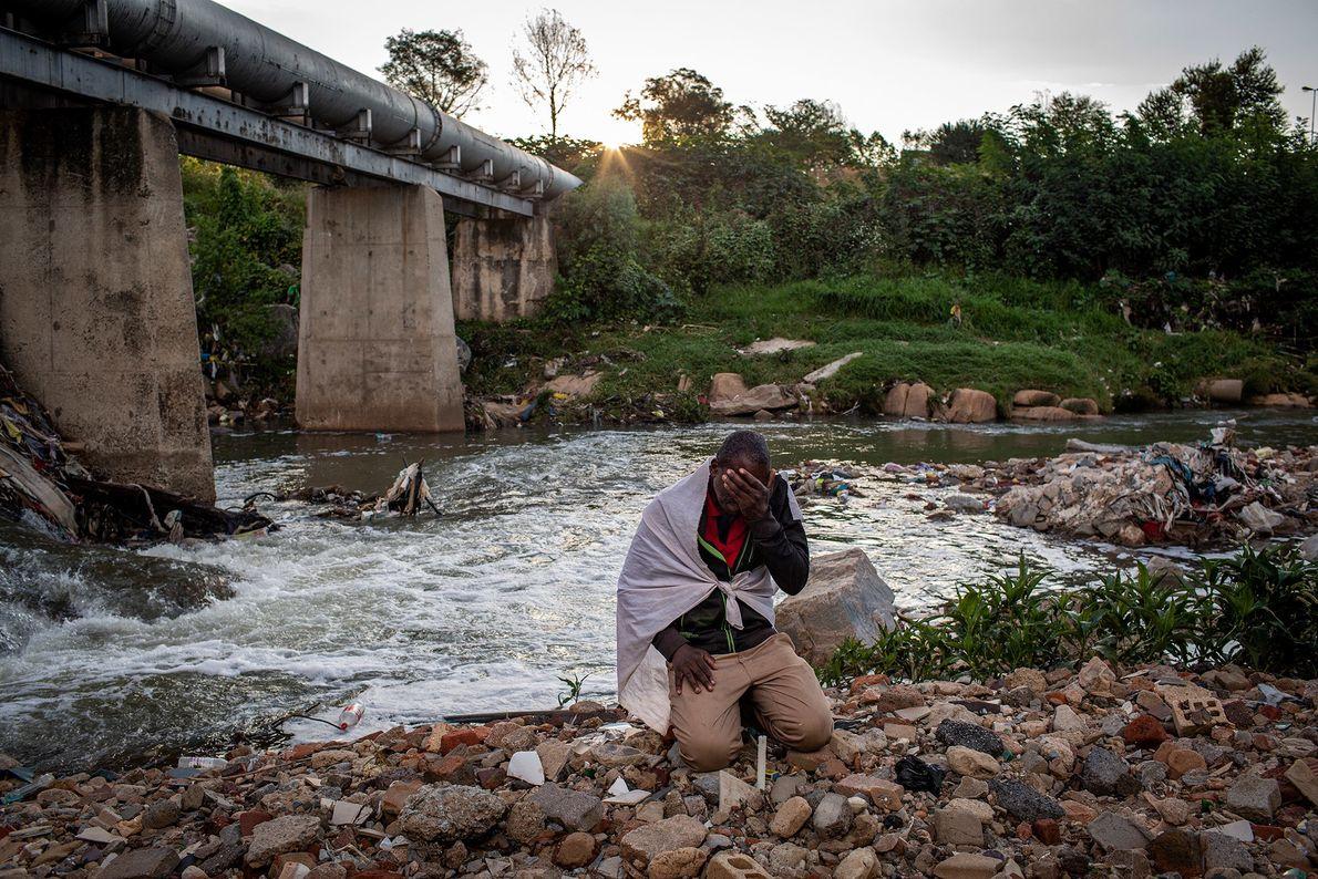 Listen Dube, 37 anos, ora ajoelhado nas margens do rio Jukskei no distrito de Alexandra, Joanesburgo, ...