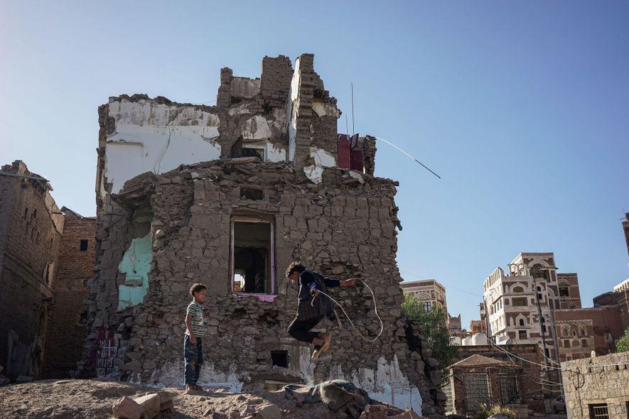 Crianças brincam logo após um bombardeio ocorrido no bairro, na capital iemenita de Sanaa.