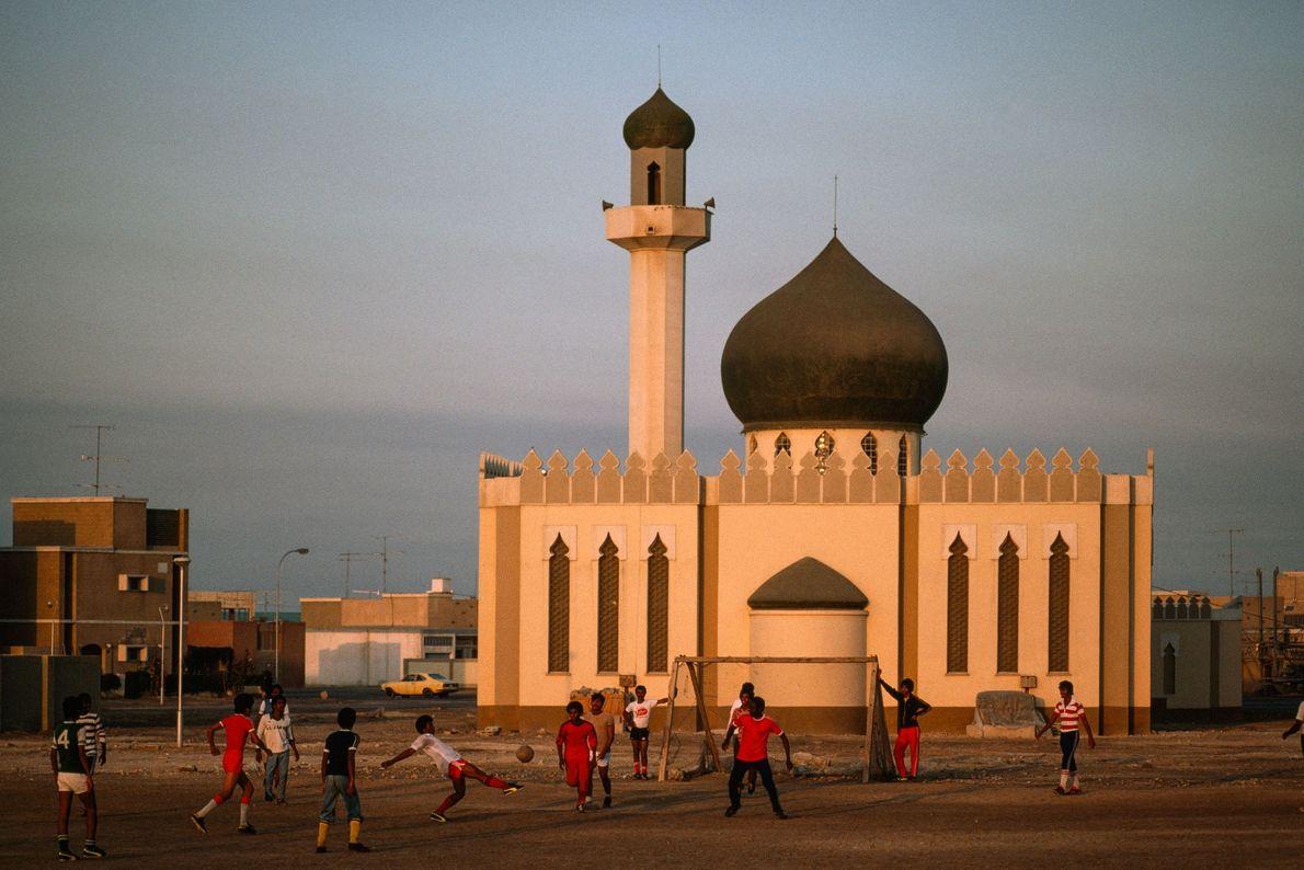 Meninos jogam futebol em frente a uma mesquita recém construída em Madinat 'Isa, Bahrein, em 1979.