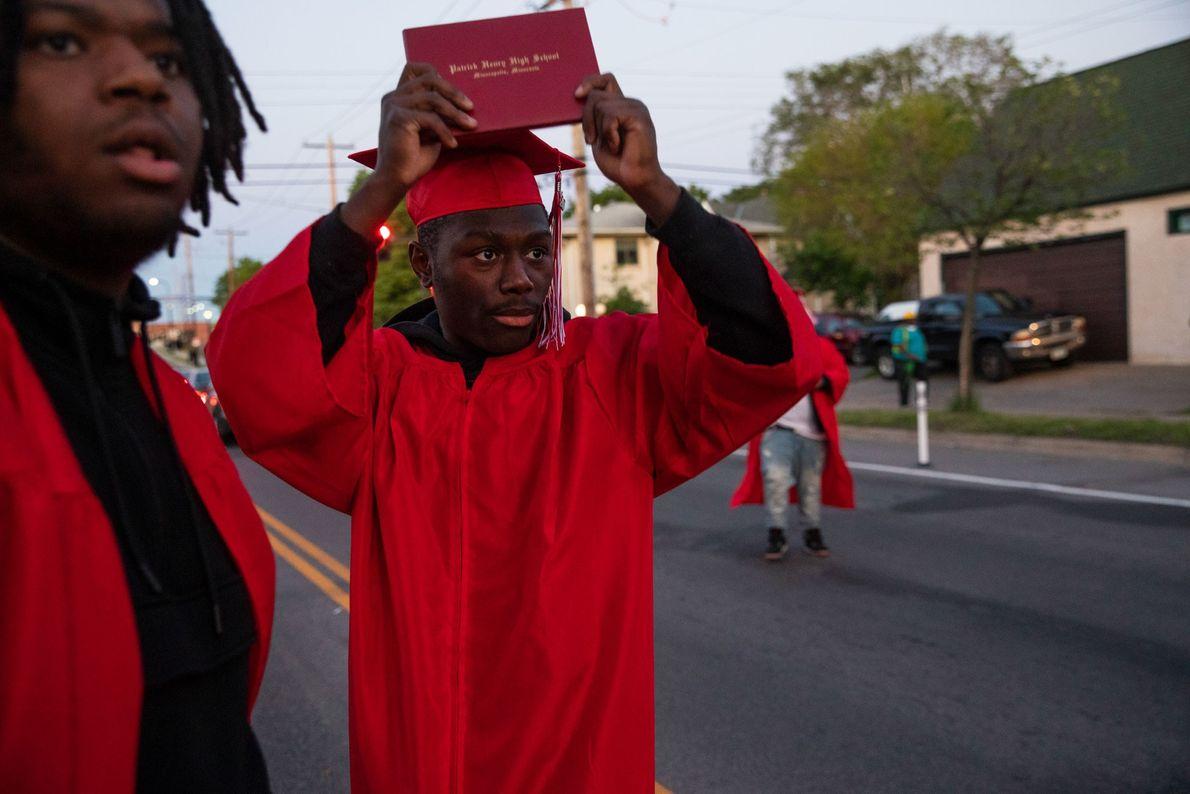 Datelle Straub levanta seu diploma quando a polícia se aproxima dos manifestantes. Ele e seus amigos ...