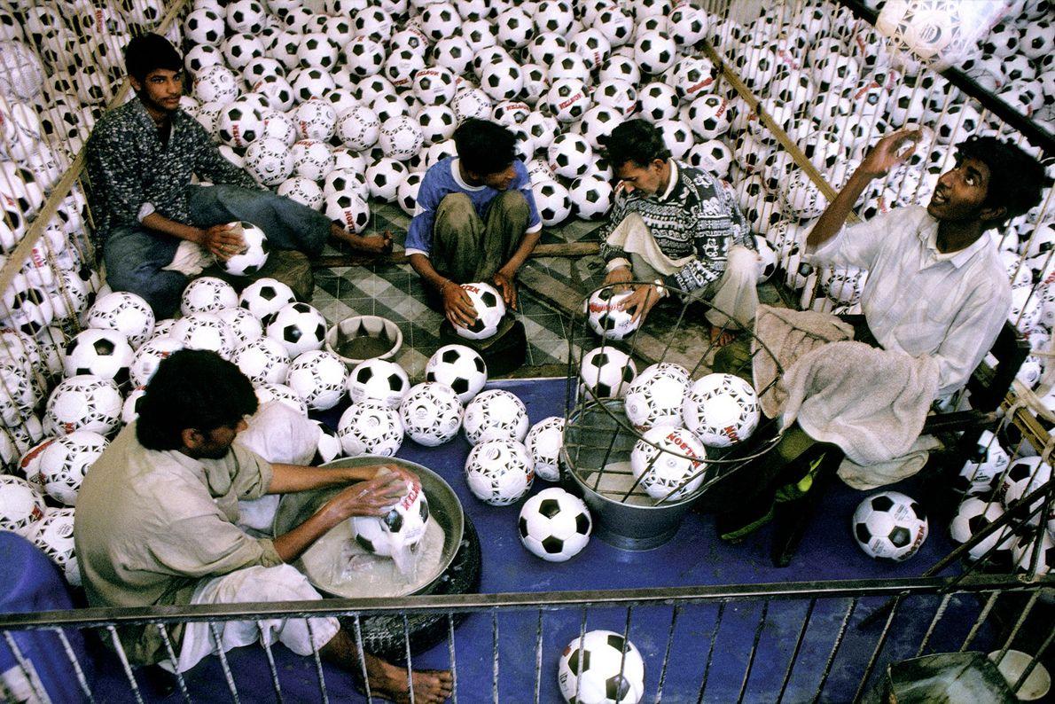 Jovens trabalhadores lavam bolas em uma fábrica de bolas de futebol em Sialkot, Paquistão, em 1998.