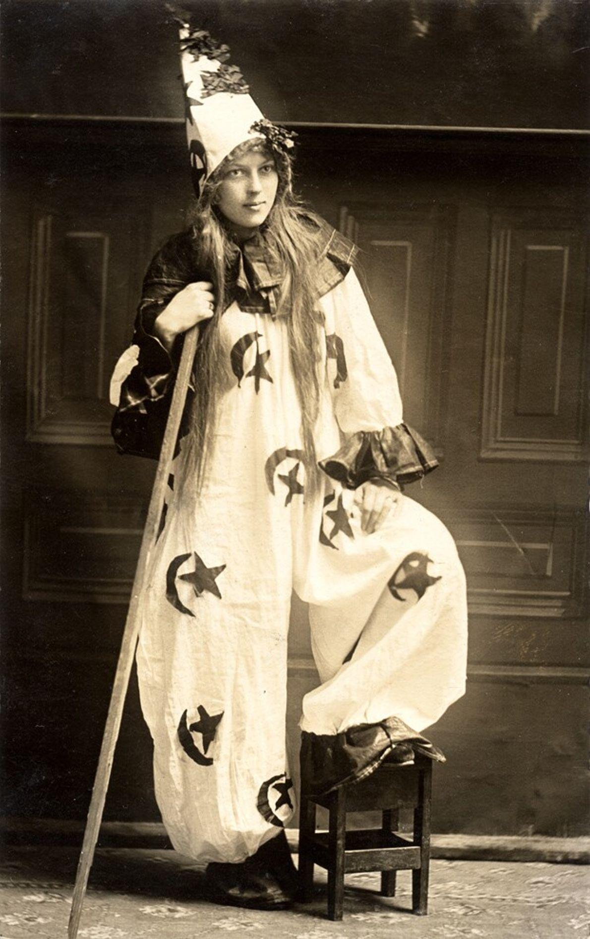 Possivelmente imitando uma bruxa, um feiticeiro ou um palhaço, a fantasia de Halloween dessa mulher em 1910 traz vários ...