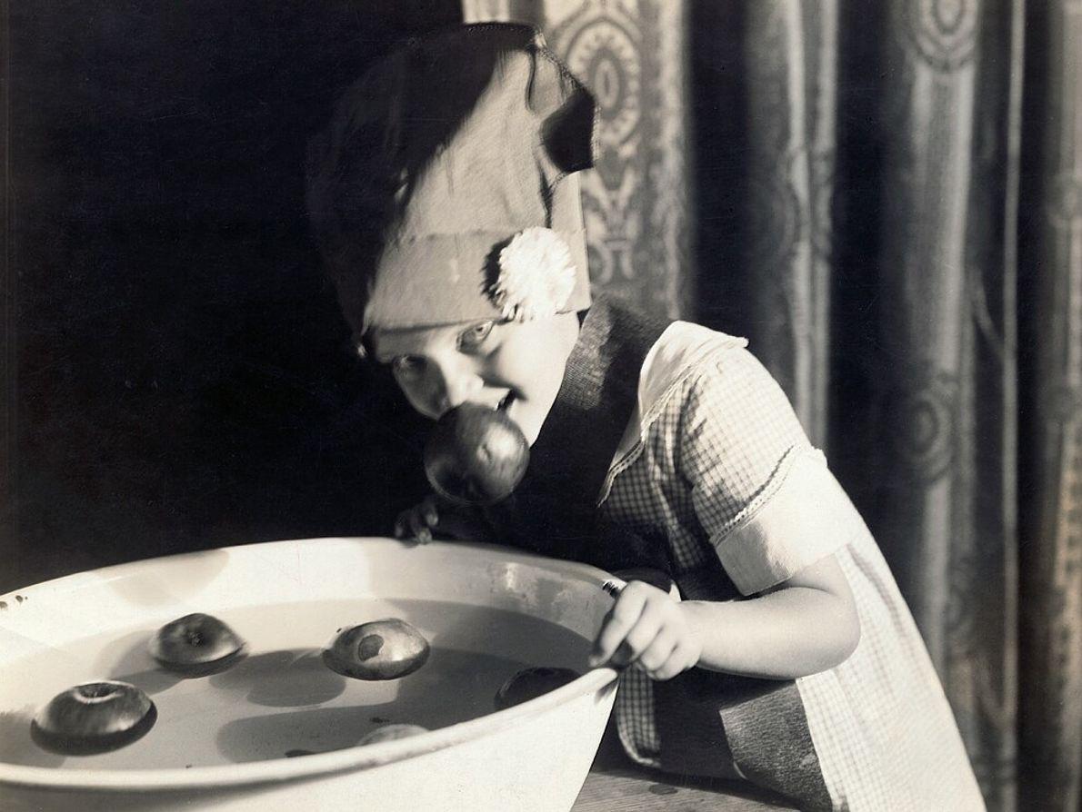 Garota abocanha maçãs para o Halloween em algum momento do início do século 20 nos EUA.