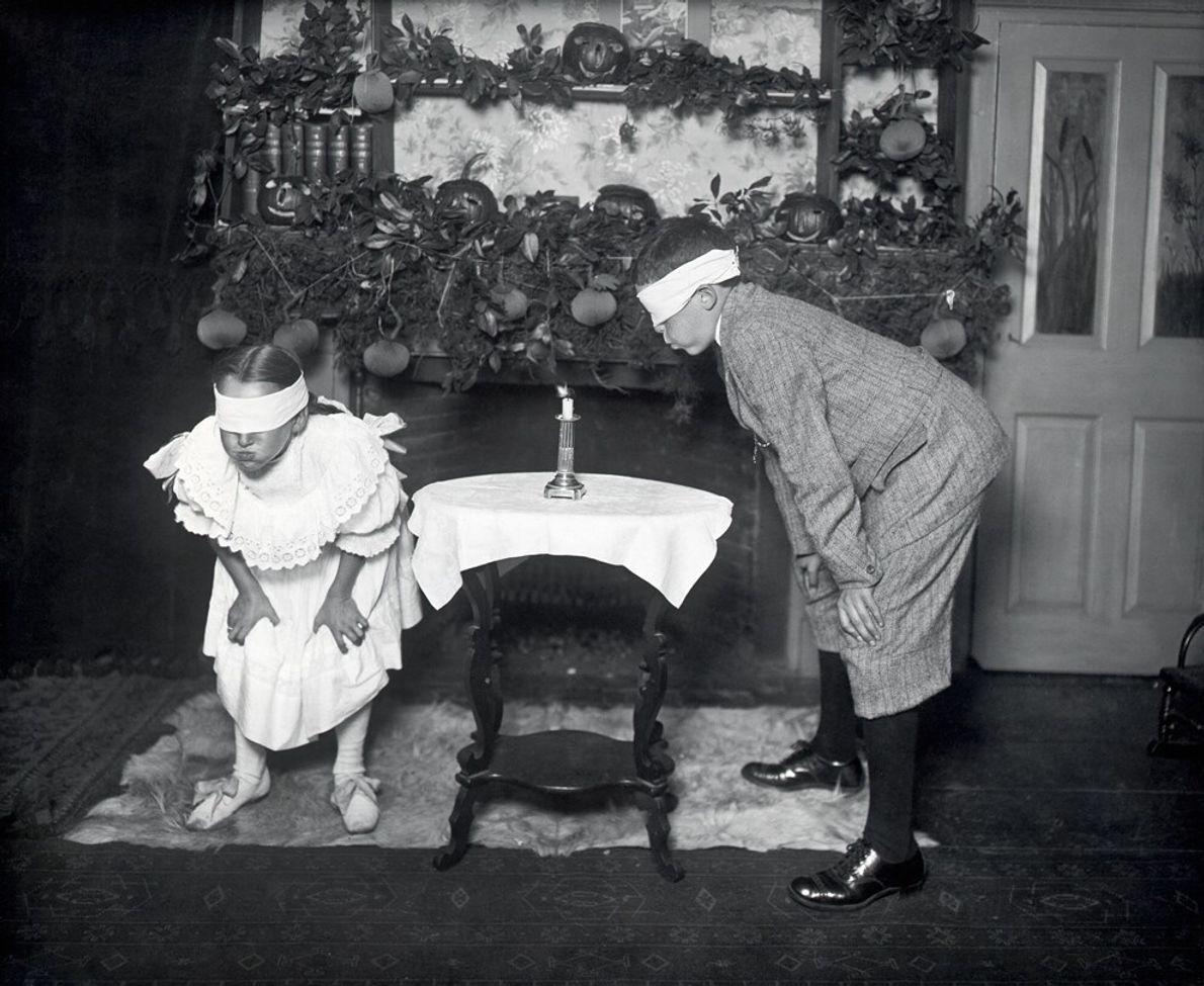Parte de um antiga tradição de Halloween nos EUA, crianças com os olhos vendados tentam apagar uma ...