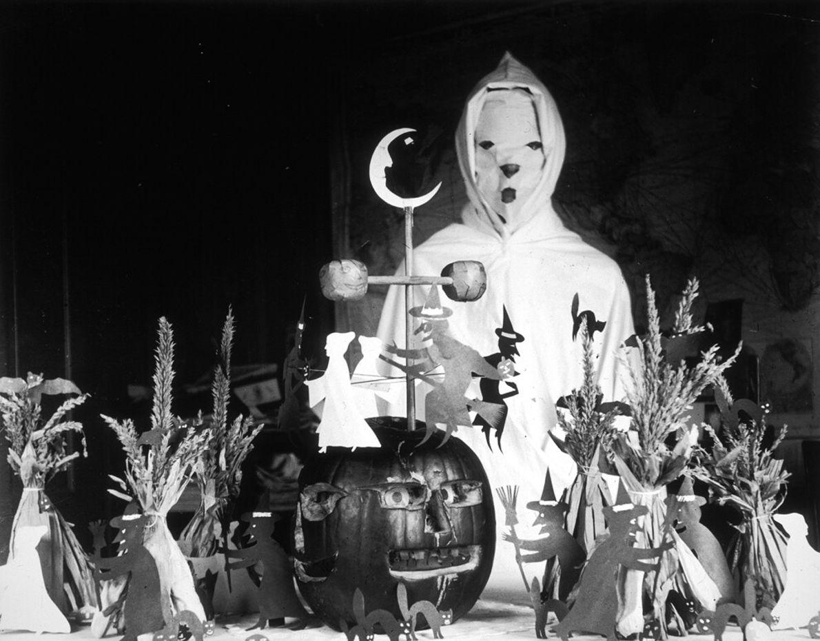 Pessoa fantasiada em uma mesa cheia de enfeites de Halloween em área rural dos Estados Unidos, em 1905. ...