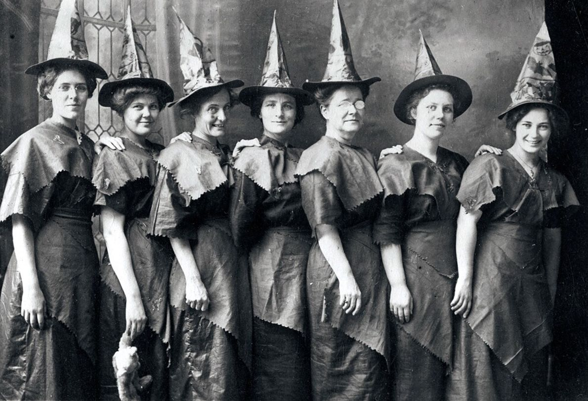 Mulheres vestindo fantasias improvisadas de bruxas fazem fila para uma fotografia nos EUA em 1910.