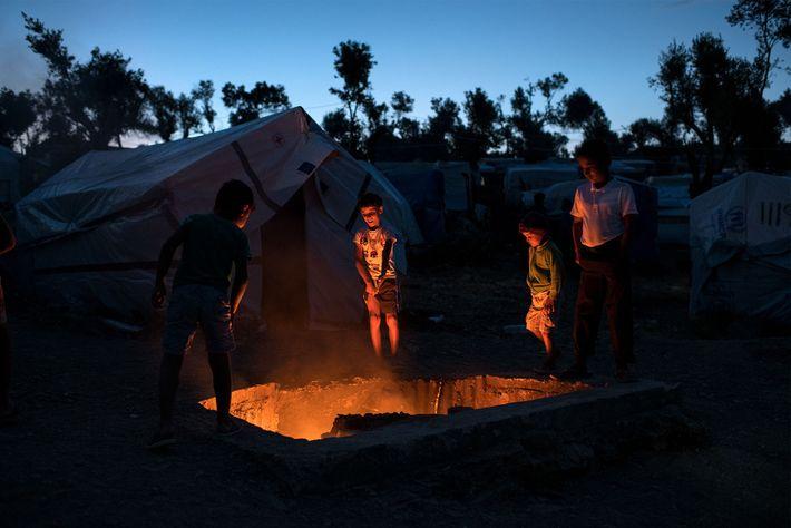 Crianças refugiadas ficam de pé em volta de uma fogueira de lixo. O fogo é usado ...