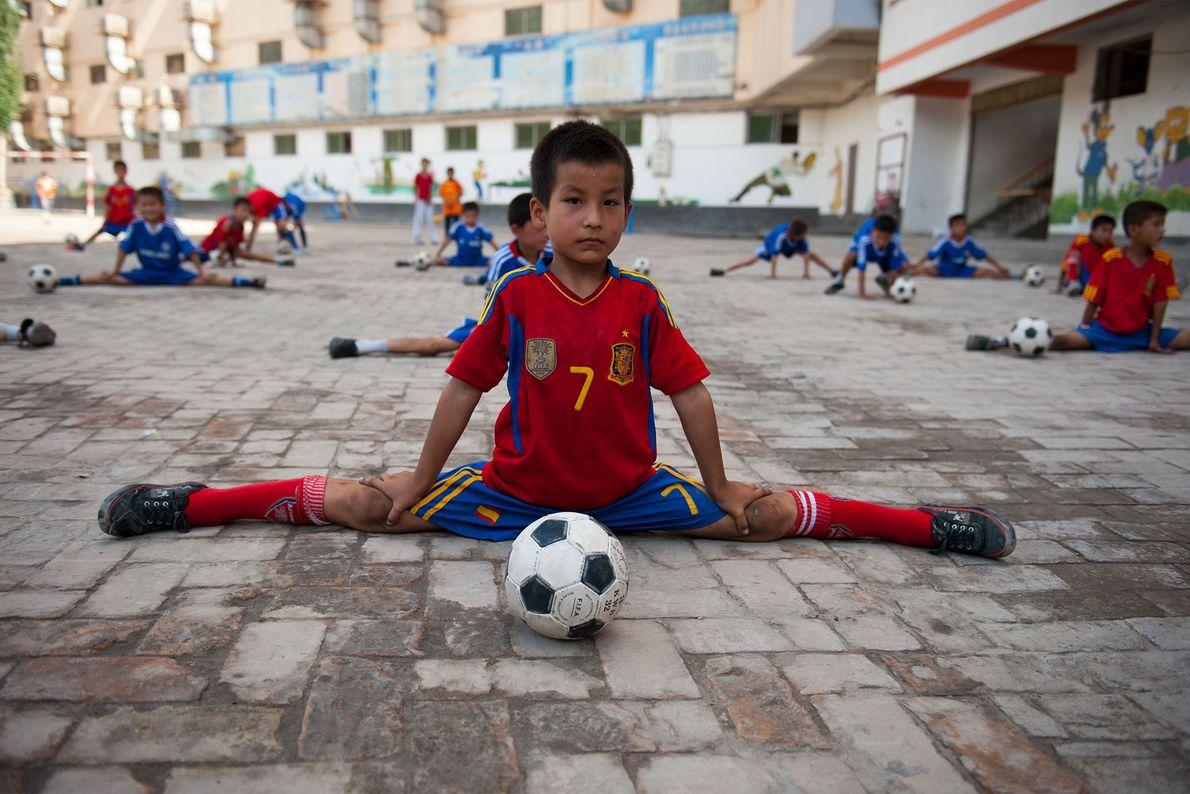 Um jovem jogador de futebol se alonga na província de Xinjiang, China, em 2011.