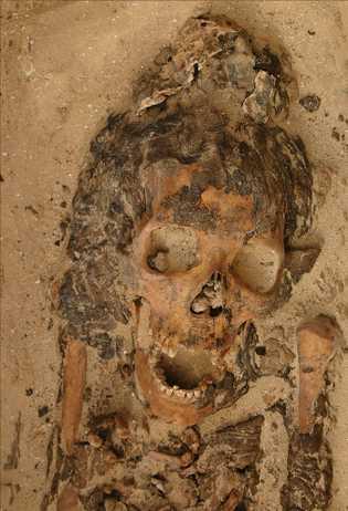 A cova de uma mulher adulta em Amarna, no Egito, com um objeto de cera de ...
