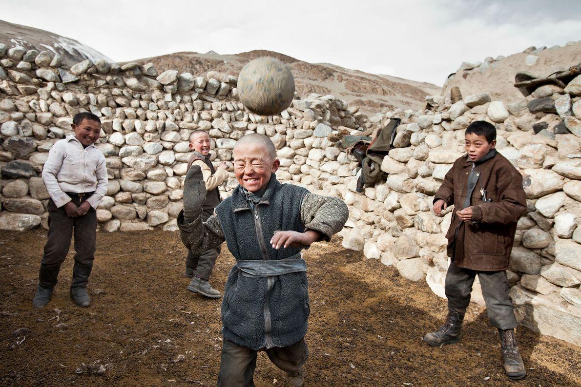 Meninos quirguizes jogam com a única bola de futebol nas Montanhas Pamir em Wakhan, Afeganistão.