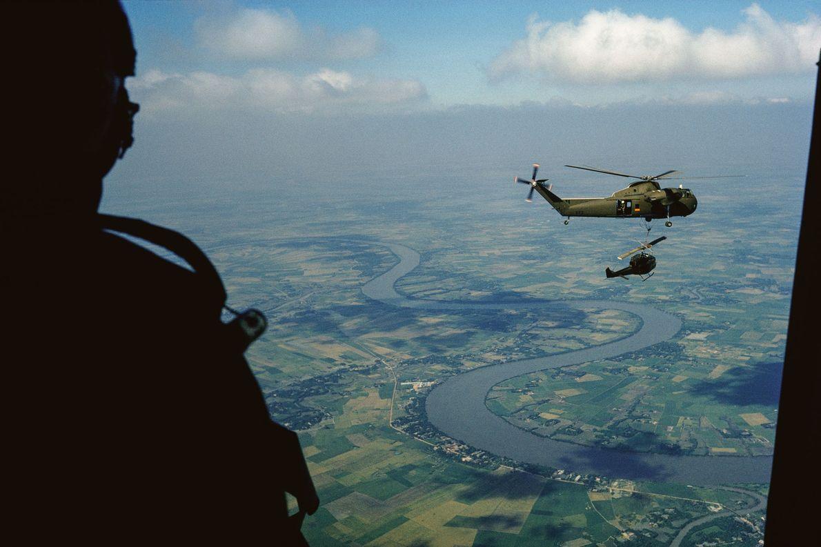 Helicóptero do Exército dos EUA transporta outro helicóptero menor sobre campos agrícolas e um canal tortuoso. ...