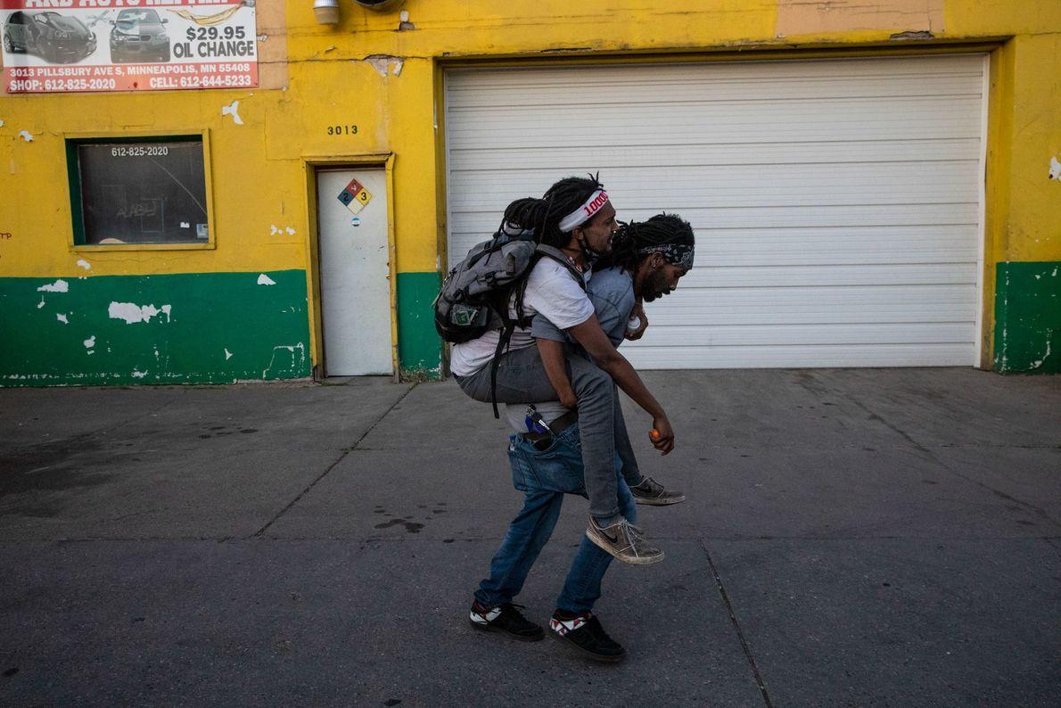 Um homem carrega um amigo ferido atingido por balas de borracha lançadas pela polícia durante os ...