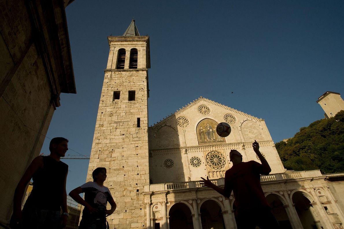 Um pequeno grupo joga futebol em frente a Catedral de Santa Maria Assunta em Úmbria, Itália.