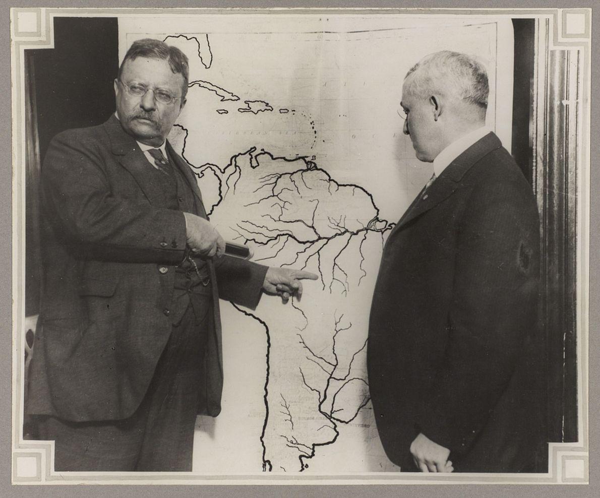 Theodore Roosevelt aponta em um mapa da América do Sul o caminho da expedição Rondon-Roosevelt.