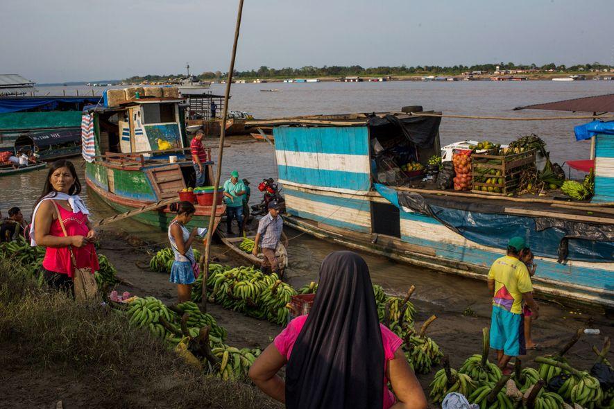 À beira do Rio Amazonas, em Leticia, as pessoas transportam as pencas de bananas. A pesca, ...