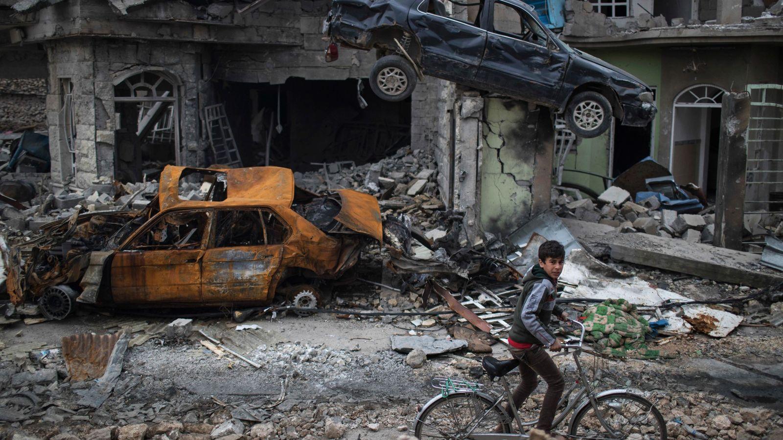 Garoto anda de bicicleta entre casas e carros destruídos em uma área liberada recentemente pelas forças ...