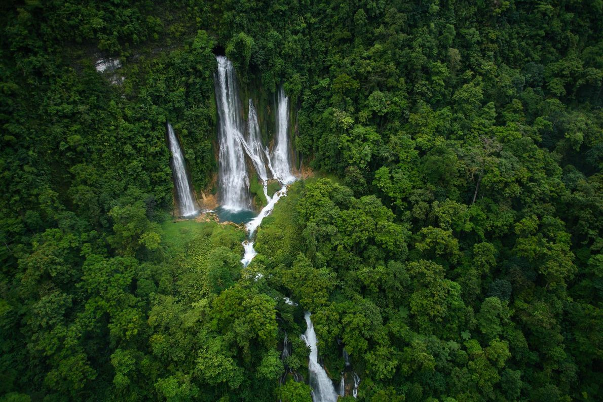 Waterfalls pour out of Mageni Cave on New Britain Island in Papua New Guinea.
