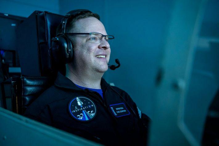 homem sorri de frente para uma tela de um simulador de voo