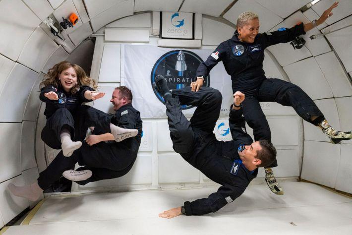 quatro pessoas flutuam dentro de um avião de teste sem gravidade