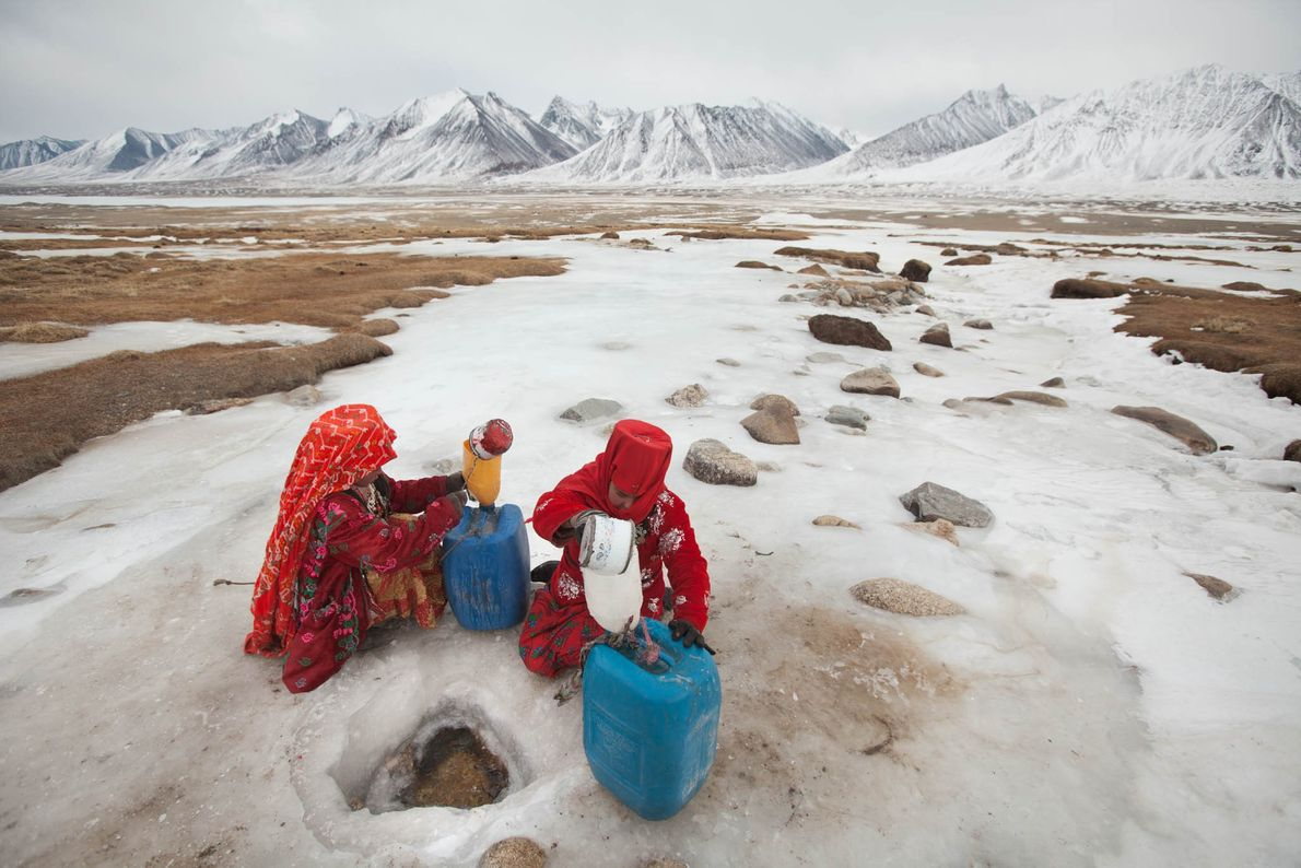 Kyrgyz girls chop a hole in a frozen spring in Wakhan, Afghanistan, to fetch water.