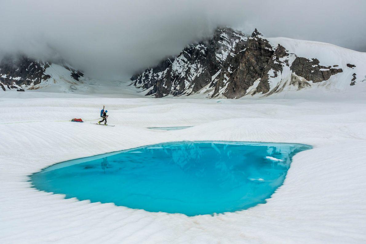 A climber skis past pools on Ruth Glacier in Alaska's Denali National Park.