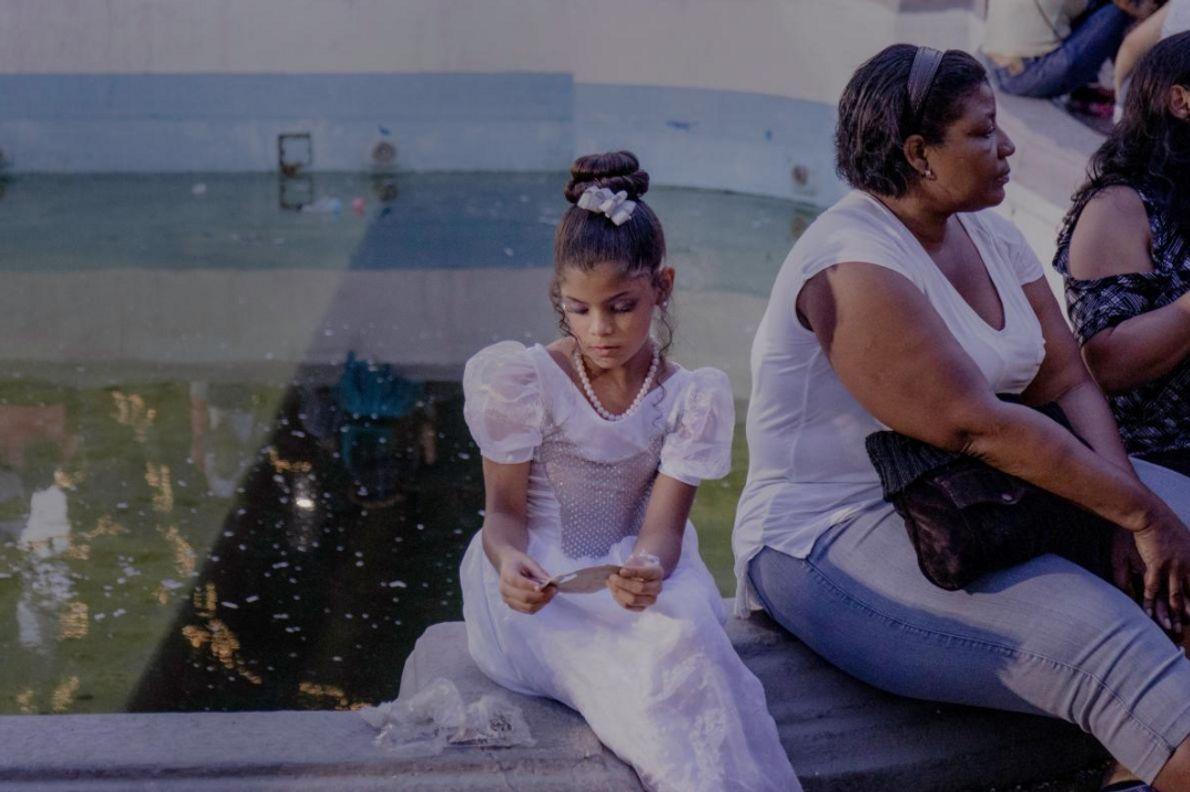 """CARACAS, VENEZUELA  Uma jovem senta-se perto da fonte na Plaza Altamira durante o carnaval da Venezuela. """"Lembro-me ..."""