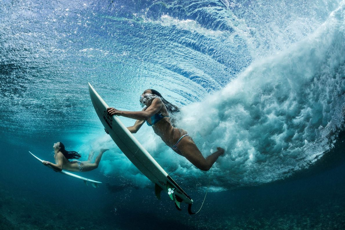 Friends dive under a wave on their way to a prime spot near their hometown of ...