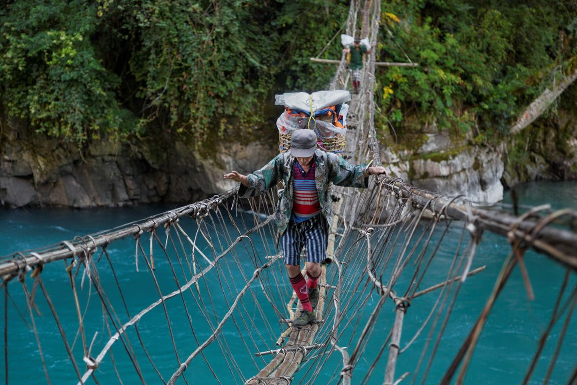 Porters ferry heavy loads across a major tributary of the Irrawaddy in Myanmar on route to ...