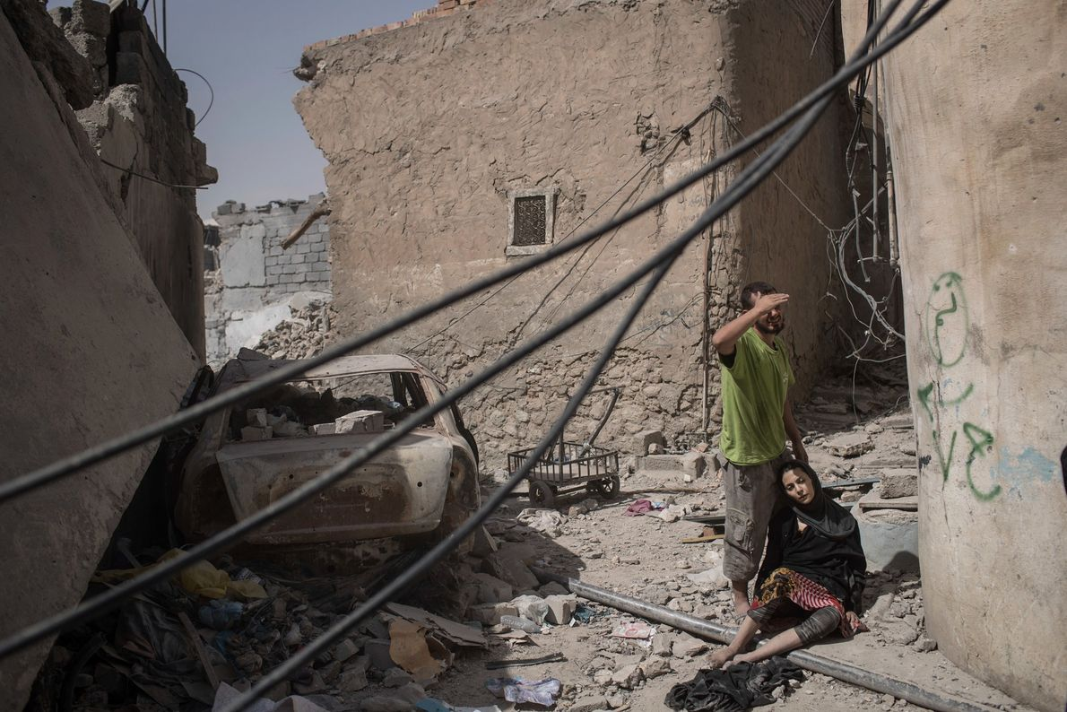 Uma mulher iraquiana exausta descansa enquanto foge por uma rua destruída, enquanto as forças armadas iraquianas ...