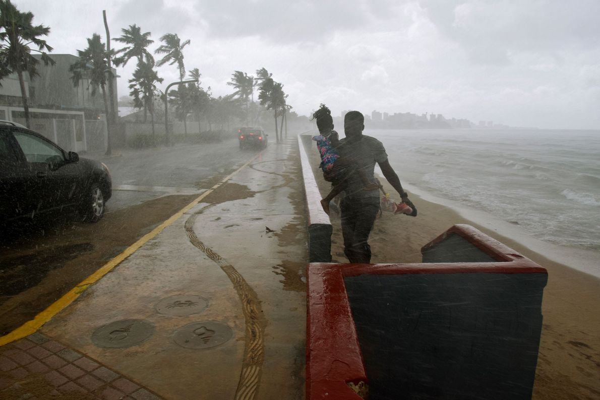 Um homem e sua filha fogem da chuva em uma praia em San Juan, Porto Rico, ...