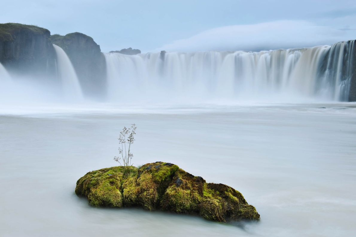 A glacial waterfall cascades over a 40-foot-high ledge in Godafoss, Iceland.