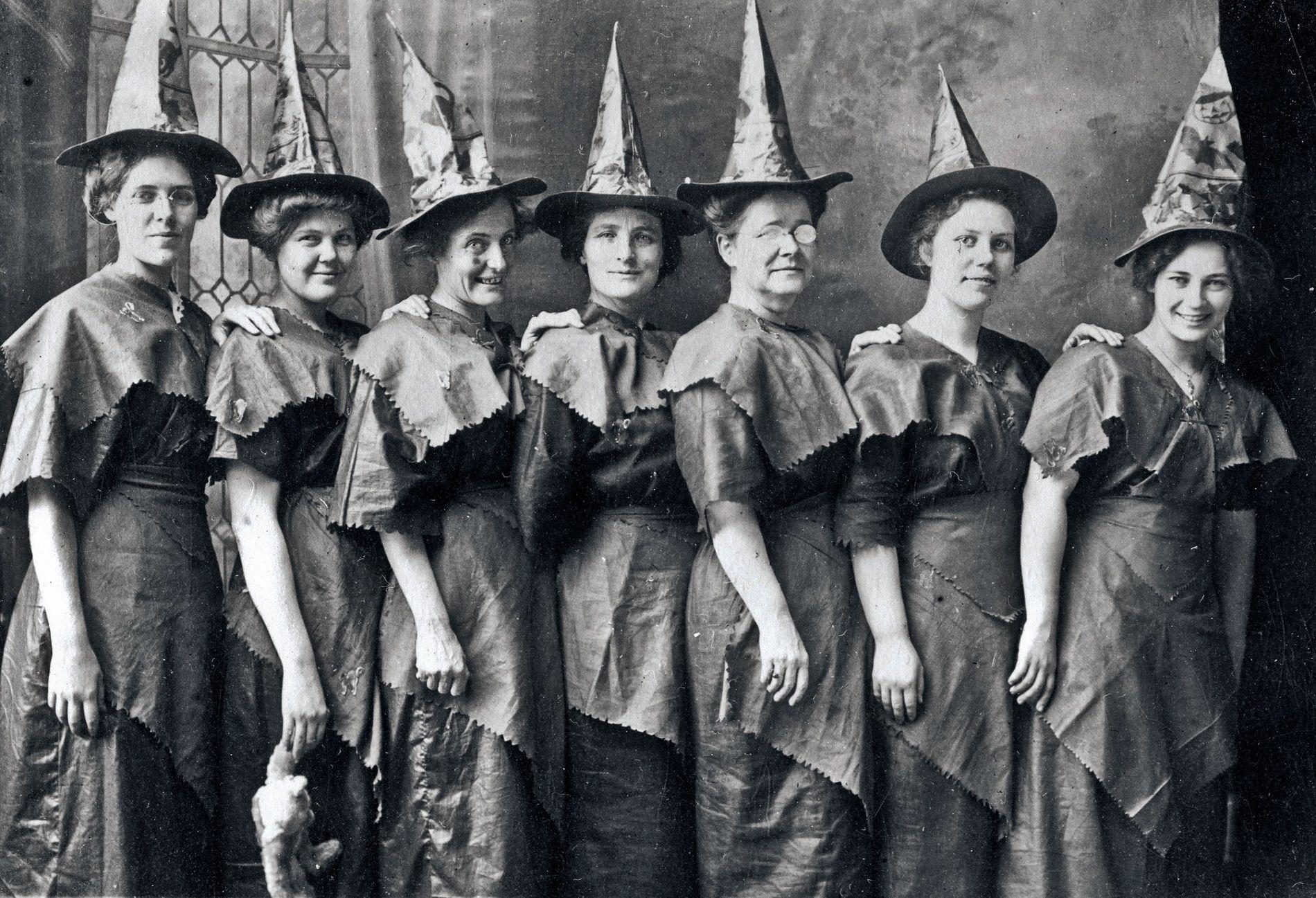 """Um encontro de """"bruxas"""" fantasiadas, reunidas para um retrato do Dia das Bruxas aproximadamente em 1910."""