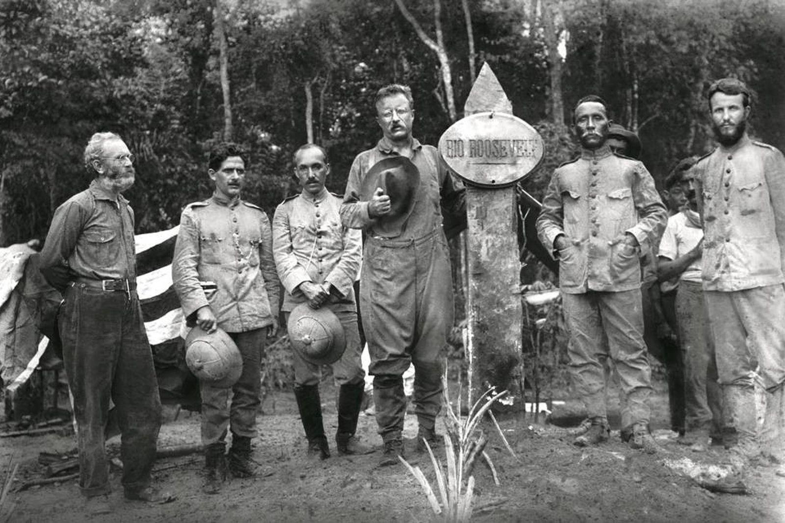 Theodore Roosevelt (à esquerda do marco), o então coronel Rondon (à direita) eoutros membros da expedição ...