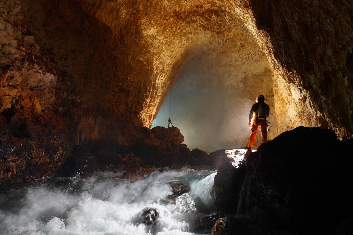 Cavers light the entrance passage of Ora Cave on New Britain Island in Papua New Guinea.