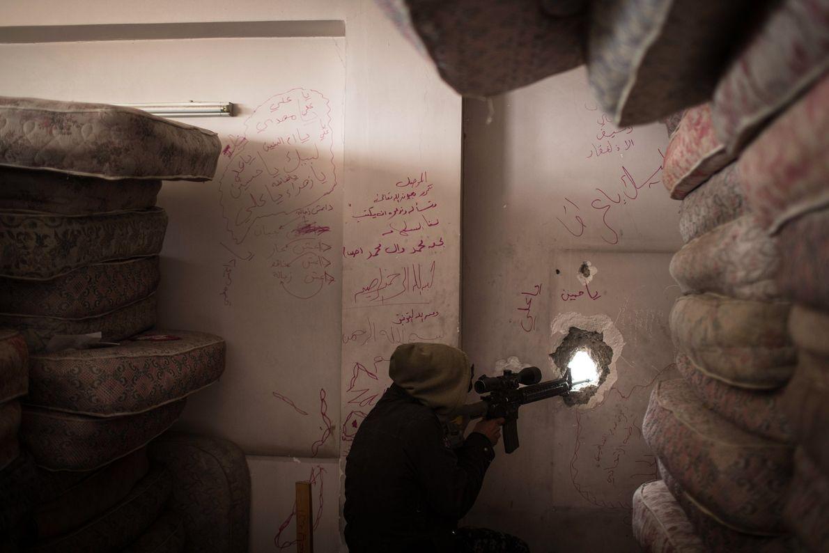 Um atirador de elite da Polícia Federal iraquiana mira posições do Estado Islâmico próximas a linha ...
