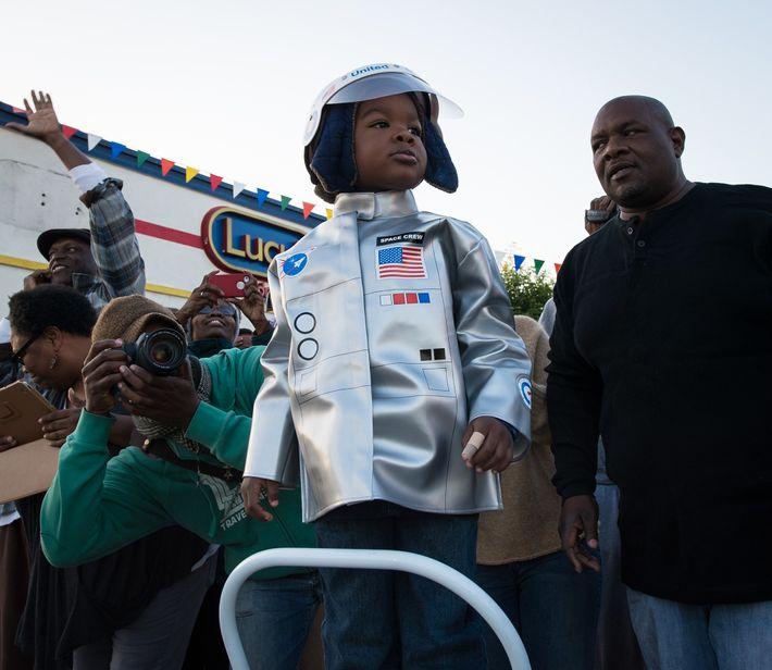 Vestido de astronauta, um espectador-mirim vê o ônibus espacial Endeavour passando a caminho de casa no ...