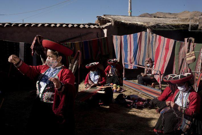 Tecelões, como Myriam Cuba Callañaupa (à esquerda), costumam expor artesanato têxtil e culinária no vilarejo de ...