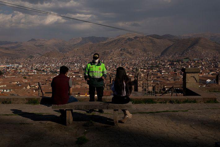 No outono de 2020, um policial pedia aos moradores locais que mantivessem distância social na esplanada ...