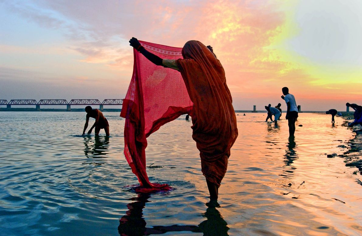 People wash clothes after Hindu prayers in a river in Ayodhya, India.