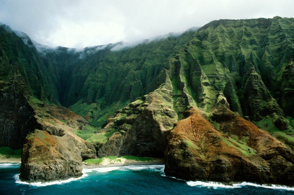 Clouds roll over the cliffs and gorges on Na Pali Coast in Hawaii.