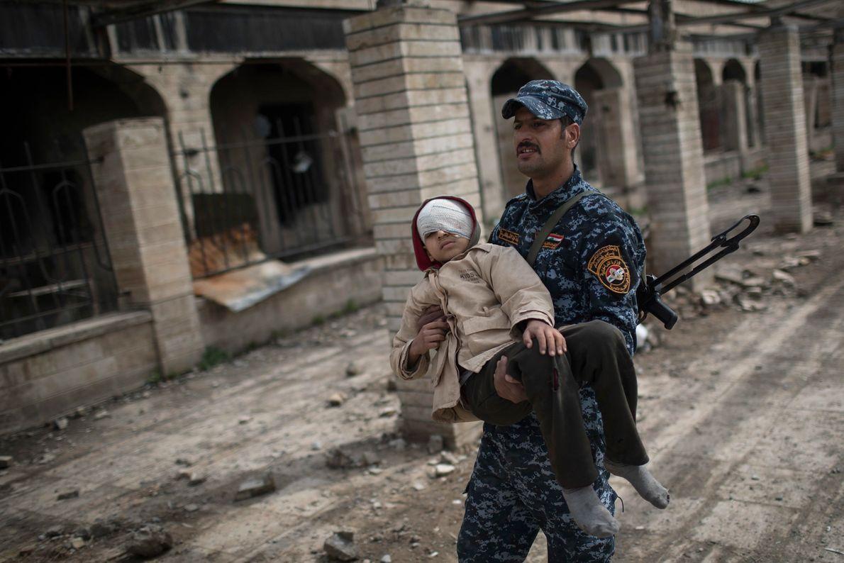 Soldado da Polícia Federal iraquiana carrega um garoto ferido por uma estação de trem destruída durante ...