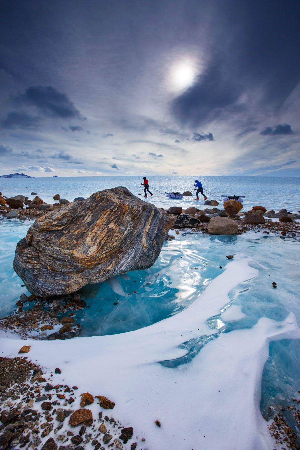 Antarctic travelers trek through a glacial blue landscape in Queen Maud Land.