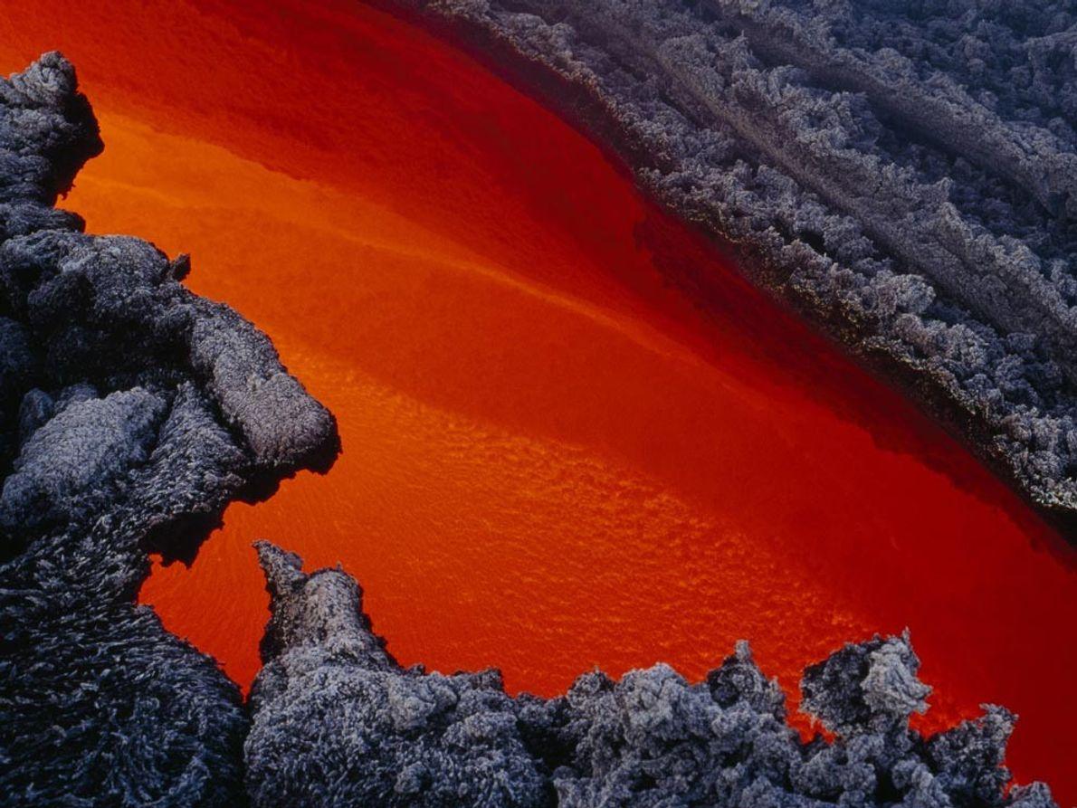 MONTE ETNA - Um rio de lava derretida flui através de um canal em lava endurecida …
